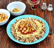 Kushari - Egyptian dish of lentils, rice, pasta, chickpeas with tomato sauce and crispy onions Stock Photo
