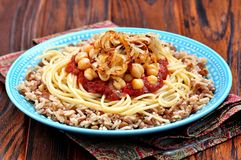 Kushari - Egyptische schotel van linzen, rijst, deegwaren, kekers met tomatensaus en knapperige uien Royalty-vrije Stock Foto