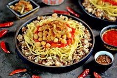 Kushari o Koushari - plato egipcio de lentejas, del arroz, de pastas, de garbanzos con la salsa de tomate y de cebollas curruscan imagen de archivo libre de regalías