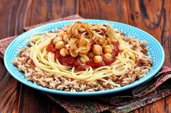 Kushari - piatto egiziano delle lenticchie, del riso, della pasta, dei ceci con salsa al pomodoro e delle cipolle croccanti Fotografia Stock Libera da Diritti