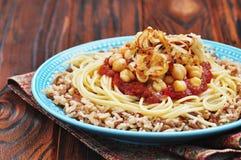 Kushari - plato egipcio de lentejas, del arroz, de pastas, de garbanzos con la salsa de tomate y de cebollas curruscantes Foto de archivo libre de regalías
