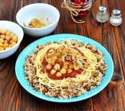 Kushari - plato egipcio de lentejas, del arroz, de pastas, de garbanzos con la salsa de tomate y de cebollas curruscantes Foto de archivo