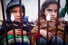 KUSHINAGAR, INDIA - DECEMBER 6, 2016: Zit de Indische kinderen en bedelt toeristen voor geld of voedsel Stock Foto's