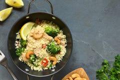 Kuskus mit Huhn, Brokkoli, Tomate und Acajoubäumen Stockfotos