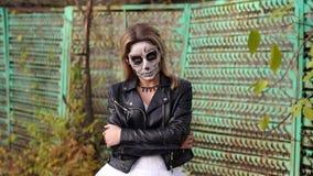 Kuslig brud med makeup i form av skallen på bakgrunden av ett gammalt staket stock video
