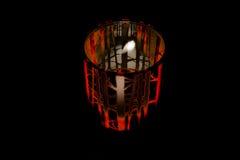 Kuslig halloween stearinljus i kruset som glöder röd med spöklika filialer arkivfoton