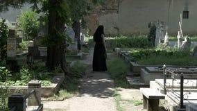 Kuslig kvinna som går i en kyrkogårdgränd till den älskade graven och förlägger en krona på grav arkivfilmer