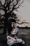 Kuslig kvinnlig häxa på bakgrund med det döda trädet Royaltyfria Foton