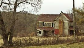 Kusligt övergett lantbrukarhem med vråk på taket Royaltyfria Foton
