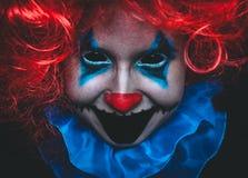 Kusligt clownslut upp den halloween ståenden på svart bakgrund royaltyfri foto
