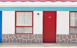 Motell med röda och blåttdörrar royaltyfria bilder