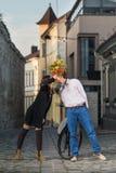 Kuss der jungen Frau und des Mannes hinter einem Blumenstrauß von Blumen stockbild