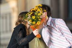 Kuss der jungen Frau und des Mannes hinter einem Blumenstrauß von Blumen lizenzfreie stockfotografie