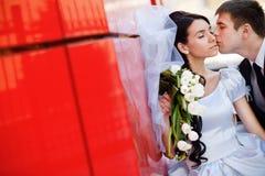 Kuss durch die rote Wand lizenzfreie stockbilder