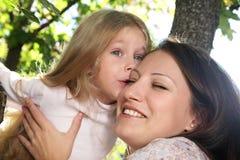 Kuss einer glücklichen Familie im Park Stockfotografie