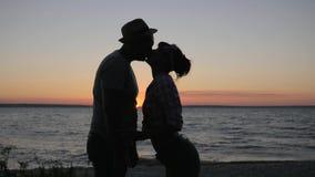 Kuss von den Liebhabern, zum von Fluss im Sonnenuntergang, glückliche Paarküsse die Küste entlangzufahren zum Dammfluß auf Hinter stock video footage