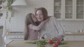 Kussen de portret mooie jonge moeder en haar leuke kleine dochter in de grote keuken, vrouw het koken en het kleine meisje haar stock videobeelden