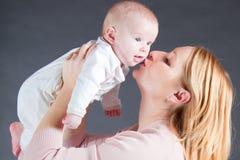 Kussende de babyjongen van de moeder Stock Afbeelding