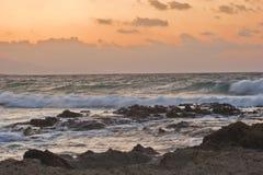 kust över stenig solnedgång Arkivfoto