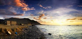 kust över stenig solnedgång Arkivbild