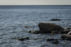 Kust av Blacket Sea på solnedgången Havet stenar och vaggar av olika format och texturer av som är svarta som, är gråa och några  fotografering för bildbyråer