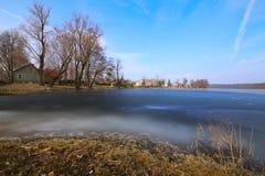 Kust av den djupfrysta sjön därefter en thorp Royaltyfri Bild