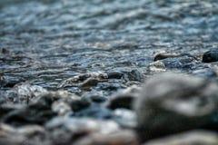 Kust av en flod med stenar och vatten med främre sikt för suddighet arkivbilder