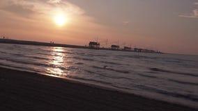 Kust av havet på gryning med trähus på diket och filmen som kör lager videofilmer