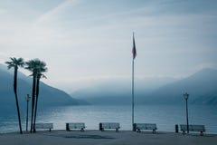 Kust av lagomaggiore med sikt på den dimmiga sjön Royaltyfri Fotografi