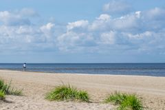Kust av stranden med den ensamma cyklisten i den ljusa soliga dagen Solig ljus dag med vita moln royaltyfri bild