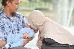Kust de Hijab moslimmoeder haar baby die door zijn vader bij openluchtpark dichtbij waterfontein bij zonnige dag houdt stock afbeeldingen