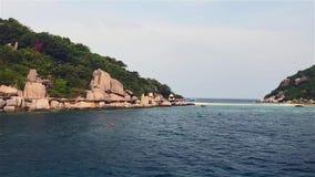 Kust in een dag van aard met eiland en blauwe golvende overzeese achtergrond stock videobeelden