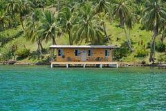 Kust- egenskap med det tropiska huset över vatten fotografering för bildbyråer