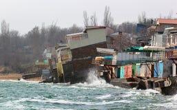 Kust- erosion - hus som byggs på svag lerajord, glider ner till havet Arkivfoton
