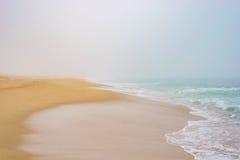 Kust för sandig strand i dimma, romantiker för hav för havsvågskum royaltyfria bilder