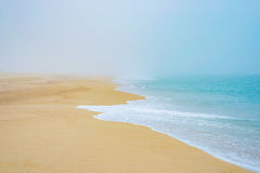 Kust för sandig strand i dimma, romantiker för hav för havsvågskum arkivbild