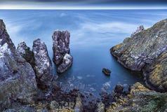 Kust- lång exponering av en stenig öppning Arkivfoto