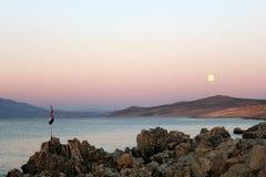 Kust med den kroatiska flaggan och måne på natten Royaltyfri Bild