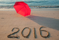 Kust met paraplu en 2016 getrokken op zand Stock Fotografie