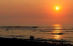 Kust- solnedgång med barnpar i kontur Arkivfoton