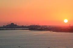 Kust- solnedgång med byggnationer i en molnfri himmel Arkivbild