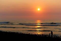 Kust- solnedgång med familjen av en vuxen människa och ett småbarn i kontur Royaltyfria Bilder