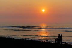 Kust- solnedgång med familjen av tre vuxna människor och ett småbarn i kontur Arkivfoton