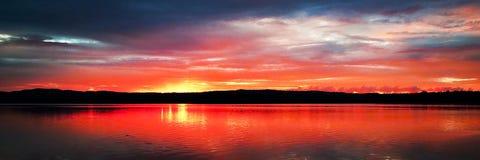Kust- soluppgångreflexioner för storartat rött moln royaltyfria foton