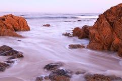 kust- stenig soluppgång Arkivfoto