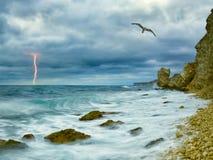 Kust van rotsen en bliksem op achtergrond stock afbeeldingen