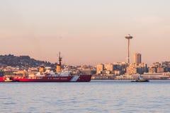 Kustbevakningfartyg i Elliott Bay med solnedgång över i stadens centrum skyskrapor i Seattle, Washington, USA royaltyfri fotografi