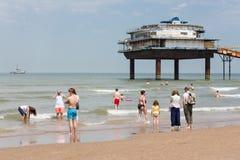 Kustbezoekers bij Nederlands strand dichtbij Pijler van Scheveningen Stock Afbeelding
