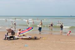 Kustbezoekers die bij Nederlands strand van Scheveningen ontspannen Stock Fotografie