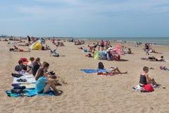 Kustbezoekers die bij Nederlands strand van Scheveningen ontspannen Royalty-vrije Stock Foto's
